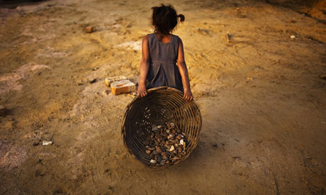 A young girl carries a basket of stones on a building site in in New Delhi, India